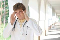 Doctor joven con un dolor de cabeza Imagen de archivo libre de regalías