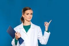 Doctor joven del estudiante con una tableta en un fondo azul que muestra muestras Imagen de archivo