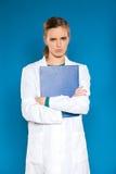 Doctor joven del estudiante con una tableta en un fondo azul que muestra muestras Foto de archivo