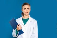 Doctor joven del estudiante con una tableta en un fondo azul que muestra muestras Imagen de archivo libre de regalías