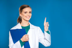 Doctor joven del estudiante con una tableta en un fondo azul que muestra muestras Imagenes de archivo