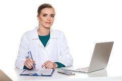 Doctor joven del estudiante que se sienta con un ordenador portátil en un fondo blanco Fotografía de archivo