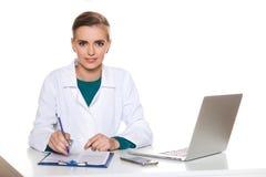 Doctor joven del estudiante que se sienta con un ordenador portátil en un fondo blanco Foto de archivo