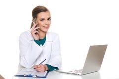 Doctor joven del estudiante que se sienta con un ordenador portátil en un fondo blanco Imagenes de archivo