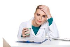 Doctor joven del estudiante que se sienta con un ordenador portátil en un fondo blanco Imagen de archivo libre de regalías