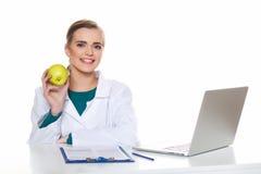 Doctor joven del estudiante que se sienta con un ordenador portátil en un fondo blanco Imagen de archivo