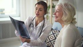 Doctor joven del médico que habla con la mujer mayor sobre su radiografía metrajes