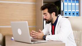 Doctor joven en el escritorio en su oficina con un ordenador portátil en frente metrajes
