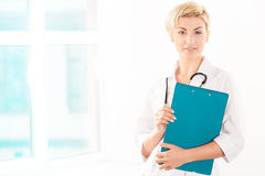 Doctor joven en la capa blanca con la tableta verde Foto de archivo libre de regalías