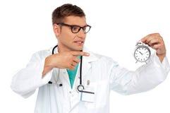 Doctor joven impactante que señala en el reloj de alarma Imagen de archivo libre de regalías
