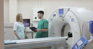 doctor joven 4K y enfermera que discuten diagnosis en un fondo de una nueva proyección de imagen de resonancia magnética metrajes