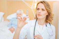 Doctor joven pensativo que mira la jeringuilla antes de hacer una inyección Imagen de archivo