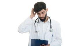 Doctor joven preocupante con la cabeza a disposición en el fondo blanco imagen de archivo