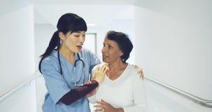 Doctor joven que ayuda al wlak paciente en el pasillo 4k del hospital almacen de metraje de vídeo