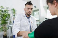 Doctor joven que comprueba a la mujer embarazada de la presión arterial Imagenes de archivo