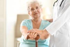 Doctor joven que lleva a cabo las manos de la mujer mayor Foto de archivo libre de regalías