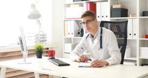 Doctor joven que mira la cámara en lugar de trabajo almacen de metraje de vídeo