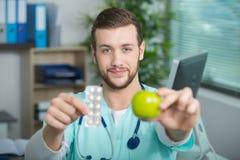 Doctor joven que muestra la manzana y las tabletas imágenes de archivo libres de regalías