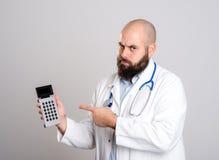 Doctor joven que señala a la calculadora de bolsillo Imagenes de archivo