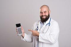 Doctor joven que señala a la calculadora de bolsillo Imagen de archivo libre de regalías