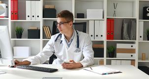 Doctor joven que sostiene el teléfono disponible y que trabaja detrás del ordenador almacen de video