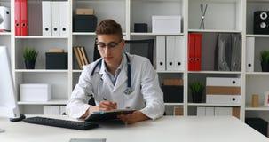 Doctor joven que trabaja con los documentos en el ordenador almacen de video