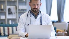 Doctor joven que trabaja en la computadora portátil almacen de metraje de vídeo