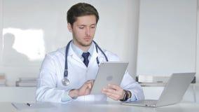 Doctor joven que usa la tableta almacen de video