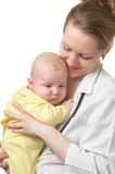 Doctor Julia and Nicolay 2. Woman the doctor in a white medical dressing gown with a stethoscope holds in hands of the small child in a yellow overalls isolated Stock Image