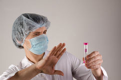 Doctor keep hourglass in one hand and show like on neutral background. Medcine concept. Royalty Free Stock Photo