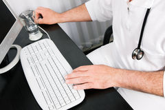 Doctor at the keyboard. Medical Doctor (only hands to be seen) doing administrative stuff at his computer Stock Image