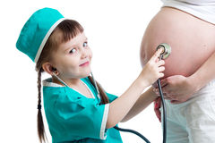 Doctor kid girl listening to pregnant mother's belly Royalty Free Stock Photos
