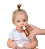 Doctor la mano de Woman usando el espray de nariz de la medicina nasal para el toddl del bebé Foto de archivo libre de regalías