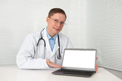 Doctor in lab coat with laptop Stock Image