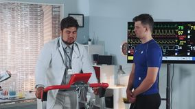 Doctor in lab coat showing athlete how properly walk on treadmill. There is a big display in the background. In Scientific Sports Laboratory stock video