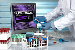 doctor in lab examining blood sample with the text multiple myeloma in screen of computer royalty free stock photography