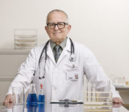 Doctor in laboratory with beaker and vials Royalty Free Stock Images