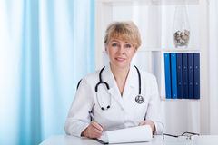 Doctor in laboratory coat with stethoscope making notes Stock Photos