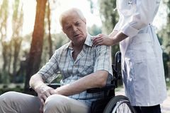 The doctor laid his hand on the sad old man`s shoulder. The doctor holds a hand on the shoulder of a sad old men sitting in a wheelchair in a summer park stock photography