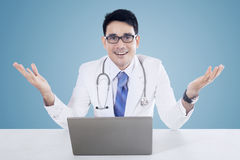 Doctor with laptop and blue background Stock Photography