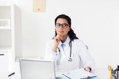 Doctor with laptop and clipboard at hospital Stock Image