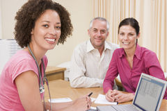 Doctor with laptop and couple in doctor's office Stock Photography