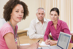 Doctor with laptop and couple in doctor's office Stock Photo