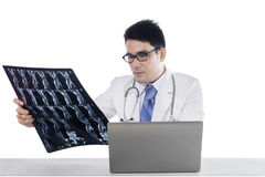 Doctor with laptop looking at x-ray Royalty Free Stock Photography