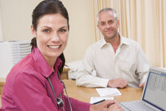 Doctor with laptop and man in doctor's office Stock Photo