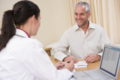 Doctor with laptop and man in doctor's office Stock Images