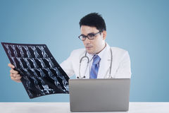 Doctor with laptop and roentgen image. Asian doctor looking at a roentgen image with laptop computer on the table Stock Image