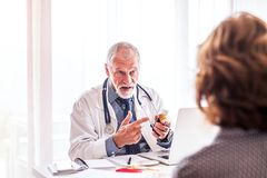 Doctor with laptop talking to a senior woman in office. Royalty Free Stock Photos