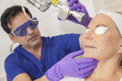 Doctor Laser Skin Treatment & Senior Woman. A cosmetic surgeon doctor giving fractional CO2 laser skin treatment to the face of a senior female women patient stock image