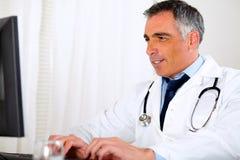 Doctor latino profesional que usa un ordenador Fotos de archivo